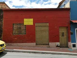 Un edificio de ladrillo rojo con una puerta roja en Casalote en Venta Santa Barbara Centro Bogota-Lote Terreno Bogota