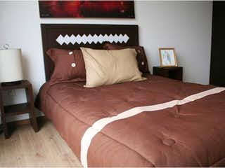 Una cama cuidadosamente hecha con almohadas y almohadas en Departamento en venta en Doctores de 2 recámaras