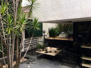 Un banco de madera sentado delante de un edificio en EXCELENTE CASA EN VENTA BOSQUES DE LAS LOMAS