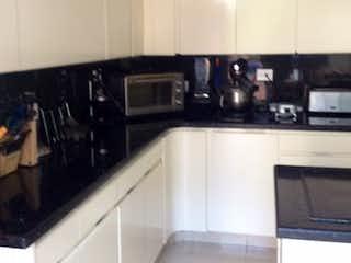 Una cocina con armarios blancos y electrodomésticos negros en Casa en venta, Santa Ana Oriental, cuenta con 6 parquederos y 3 habitaciones.