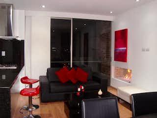 Una sala de estar llena de muebles y una televisión de pantalla plana en Apartamento en venta en Chicó Reservado de 2 hab. con Bbq...