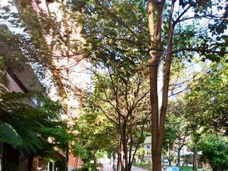 Una calle de la ciudad con un banco y árboles en Apartamento en venta en El Nogal de 2 habitaciones