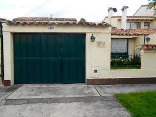 Un edificio de ladrillo blanco con una puerta verde en Casa en Venta VILLA MAGDALA