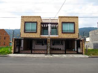 Un edificio con un banco y un edificio en el fondo en 104951 - Casa en Venta en Tenjo