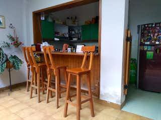 Una cocina con una mesa de madera y sillas en Casa en venta en Bolivariana de 4 alcobas