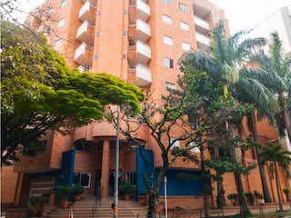 Un edificio alto con un árbol en el fondo en Venta De Apartamento en Laureles