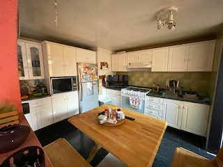 Una cocina con suelos de madera y electrodomésticos blancos en Casa en venta en Azcapotzalco