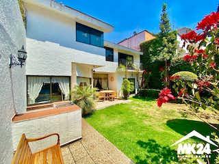 Una casa que tiene un árbol en ella en HERMOSA CASA EN COLINAS DEL BOSQUE EN $11,980,000MN. A DOS MINUTOS DE PERIFERICO