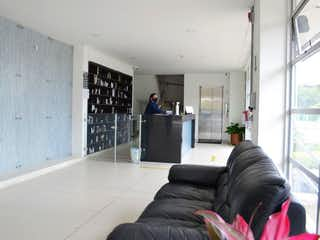 Una persona sentada en un sofá en una sala de estar en Apartamento En Venta En Bogota San Antonio Norte