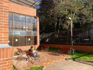 Una persona sentada en un banco frente a un edificio en Apartamento en Venta ATABANZA