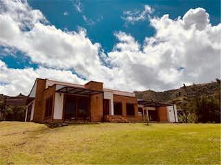 Una casa que tiene un edificio en el fondo en Venta de Finca en Guarne, Antioquia