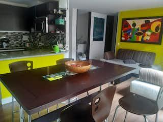 Una cocina con sillas de mesa y un televisor en Venta/Arriendo de apartamento en Pasadena-Suba, Bogotá
