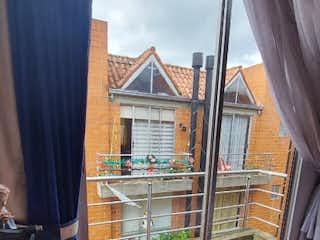 Un hombre está mirando por una ventana en Casa en venta en Casco Urbano Mosquera de 93m² con Jardín...