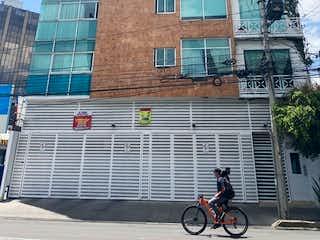 Una persona montando una bicicleta delante de un edificio en EN VENTA DEPARTAMENTO EN AVENIDA COYOACAN. COLONIA ACACIAS .