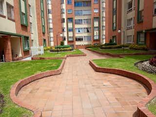 Un gran edificio de ladrillo con un banco de parque en Apartamento en Venta GRATAMIRA