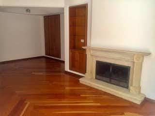 Una sala de estar con suelos de madera y una chimenea en Vende apartamento El Nogal Bogota