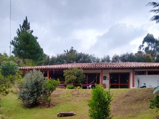 Una vista de un campo con un edificio en el fondo en Finca San Antonio de Pereira - Carmen de Viboral