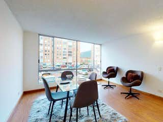 Un hombre sentado en una silla en una sala de estar en Apartamento En Venta En Bogota Verbenal