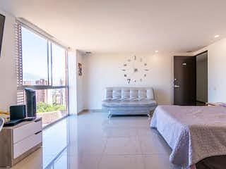 Un dormitorio con una cama y una lámpara de araña en Apartaestudio en Venta LOMA DEL CAMPESTRE