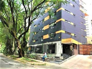 Un edificio alto sentado al lado de un árbol en Apartamento en Venta BOSQUES DE ZUñIGA