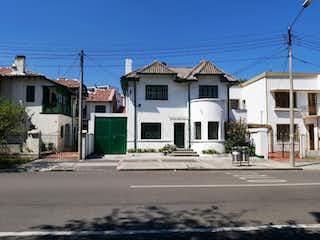 Un edificio blanco con un letrero en la calle en 103630 - Casa de Interés Arquitectónico en Teusaquillo.
