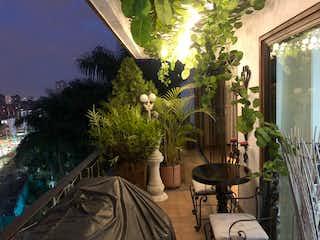 Una sala de estar llena de muebles y flores en Espectacular apartamento remodelado para la venta en el Poblado