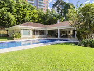 Una casa que está sentada en la hierba en CASA A LA VENTA CON PISCINA EN PLENO CORAZN DEL POBLADO