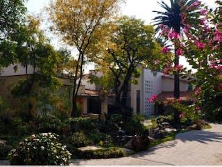 Un jardín con un árbol y un edificio en Casa en Condominio La Rosaleda / San Ángel