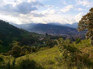 Una vista panorámica de un valle con montañas en el fondo en 3702900AM Venta de lote en Envigado, Antioquia