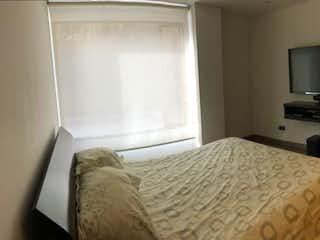 Un dormitorio con una cama y un televisor en VENTA HERMOSO APARTAMENTO BOSQUE MEDINA