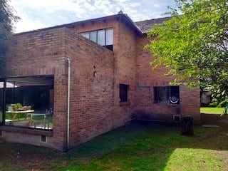 Un edificio de ladrillo con un banco delante de él en Casa Campestre En Venta En Chia Guaymaral