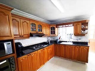 Una cocina con armarios de madera y encimeras de granito en  Venta de Casa en Belen nogal - Medellín