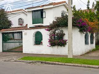 Un edificio blanco con un jardín de flores blancas en Casa esquinera en VENTA en las Villas