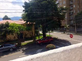 Un coche conduciendo por una calle cerca de un semáforo en Casa En Venta En Bogota La Calleja