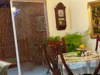 Una habitación con una mesa y sillas en ella en El Caney