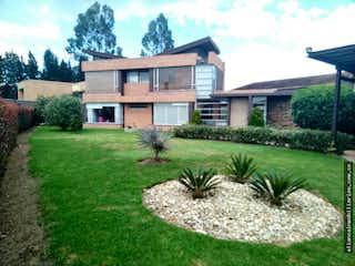 Una casa grande con un árbol en el medio en Casa Campestre 4H, CBS, Zona Verde Amplia- Terraza con espacio para BBQ,