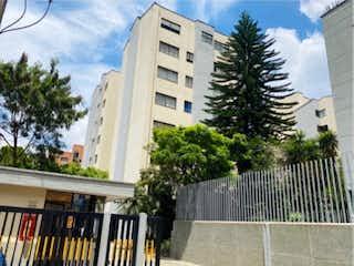 Un edificio alto con un árbol en el fondo en Apartamento en Venta MILLA DE ORO