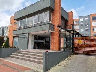 Un edificio de ladrillo con un letrero en la calle en Vendo Lindo Apartamento Hayuelos
