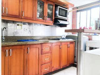 Cocina con armarios de madera y horno de microondas en Venta Apartamento Belen Rincon Medellín