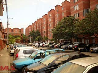 Una calle de la ciudad llena de coches y edificios estacionados en Laureles De Terranova