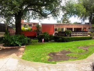 Un jardín con un banco y algunos árboles en Las Flores, Tlacopac, Casa en venta