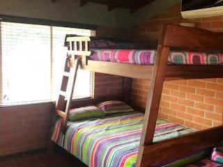 Una cama sentada en un dormitorio junto a una ventana en Casa en Venta en Santa Fe de Antioquia, Colombia.
