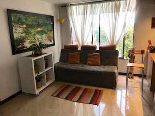 Una sala de estar llena de muebles y una televisión de pantalla plana en Apartaestudio en venta en Teusaquillo, 51mt