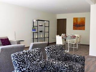 Una sala de estar llena de muebles y un reloj en Arbolada Tepepan