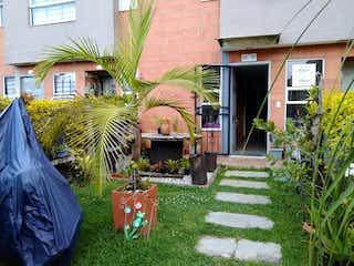 Una casa con un banco y un árbol en Venta Casa en El Carmen de Viboral