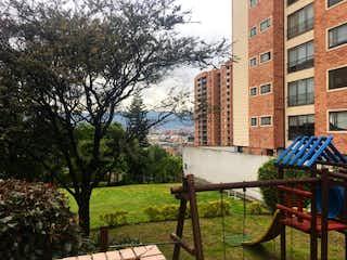 Un banco de madera sentado delante de un edificio en 108823 - Apartamento Venta  Gratamira Bogotà