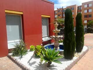 Una planta delante de una casa roja en VENDO LINDO APTO MAZUREN