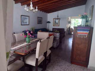 Una sala de estar llena de muebles y flores en Casa en Laureles, Medellin