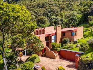 Un edificio de ladrillo rojo con un banco delante de él en Casa En Venta En Bogotá La Floresta Norte