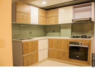 Una cocina con armarios de madera y un horno de cocina en Apartamento en venta en La Chinca, La Estrella.